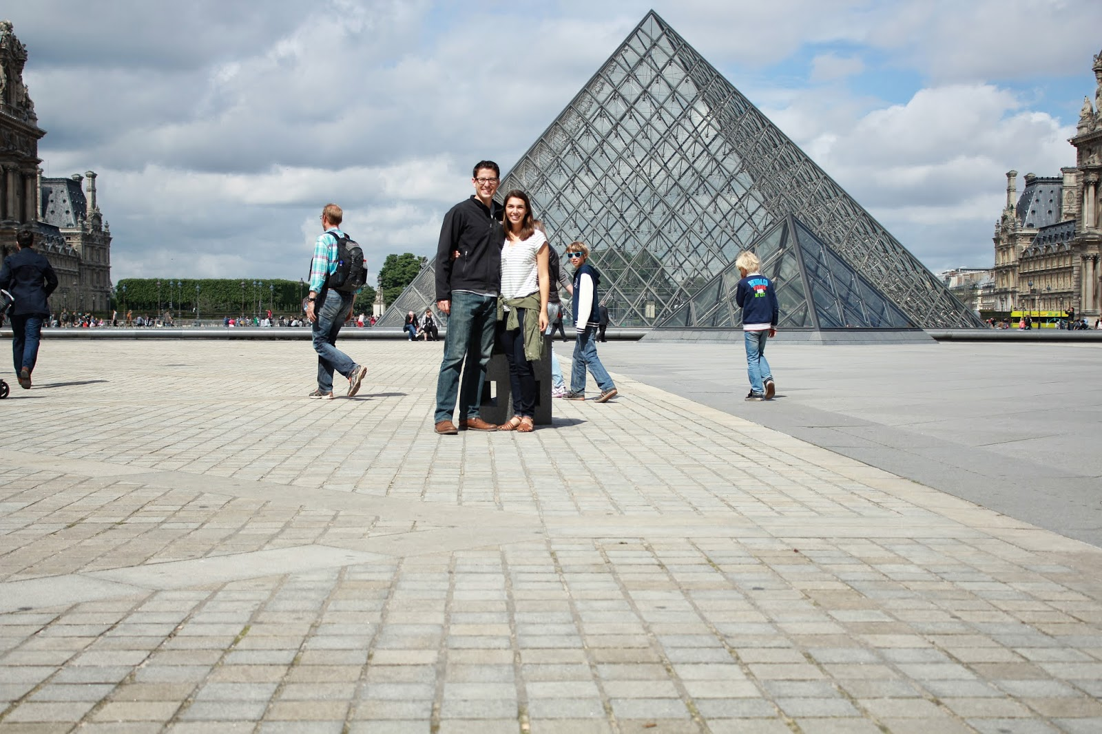 A couple in front of the Louvre Museum