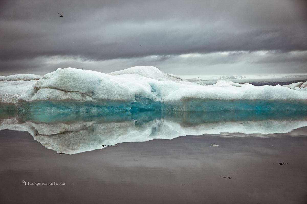 Blaues Eis schimmert aus dem Innern eines Eisbergs