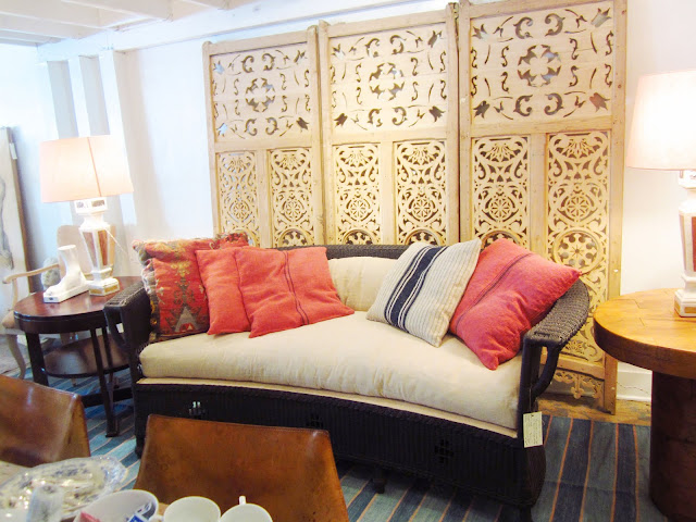 Carved wood screen is backdrop for a wicker sofa with pillows made out of vintage linens on a striped rug