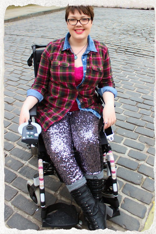 Young woman in an electric wheelchair, viewed head-on, wearing sparkly leggings, tall boots, and a plaid shirt.