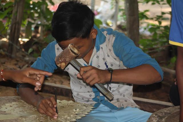 Un élève au travail sur une pièce de cuir