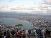 View of Hakodate during the day from Mt Hakodate with a small crowd of people in the foreground