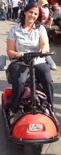 Descrição da imagem: Francelene andando pelas ruas com sua cadeira motorizada.