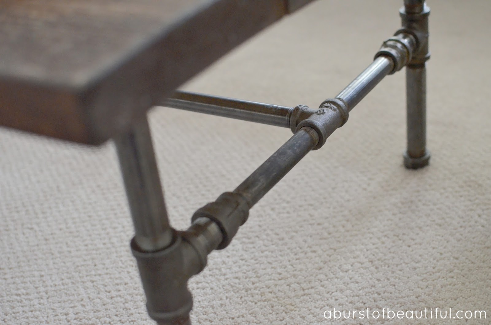 Diy rustic industrial pipe coffee table a burst of beautiful for Rustic pipe table