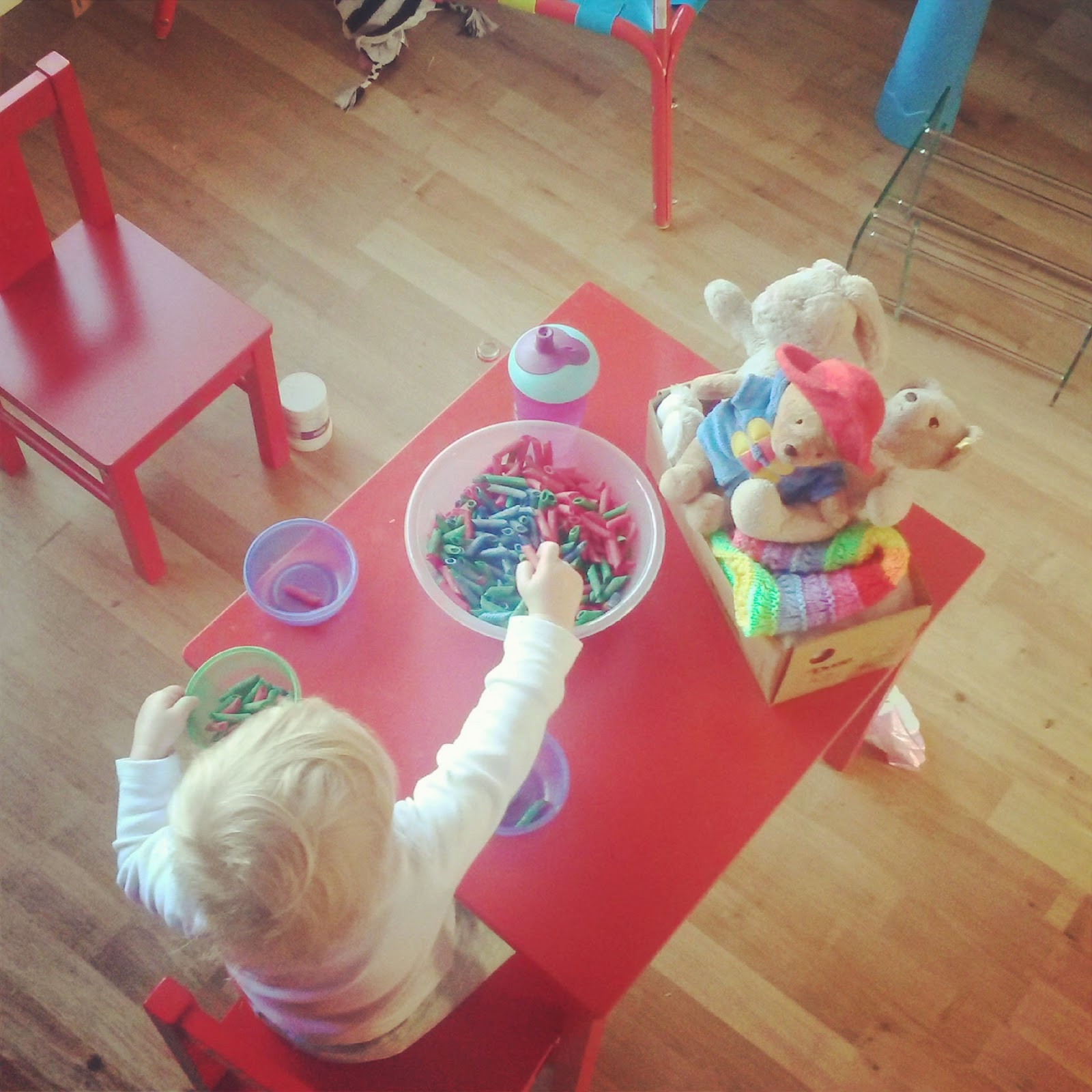sorting coloured pasta into bowls.