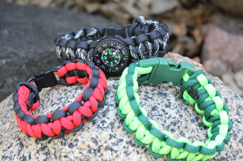 3 paracord survival bracelets sitting on a rock