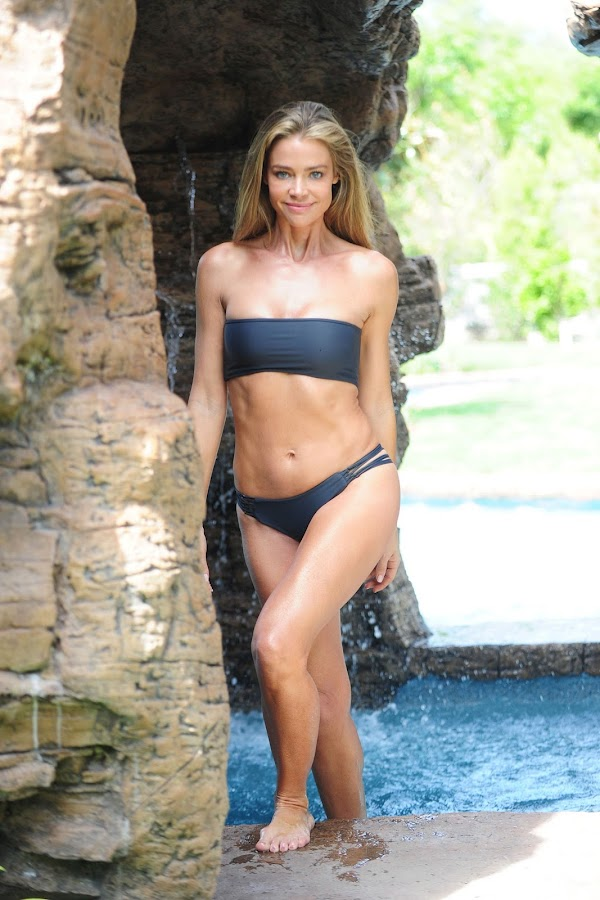 Denise Richards posing in a black bikini