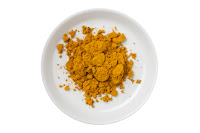 Bowl of turmeric powder on white background