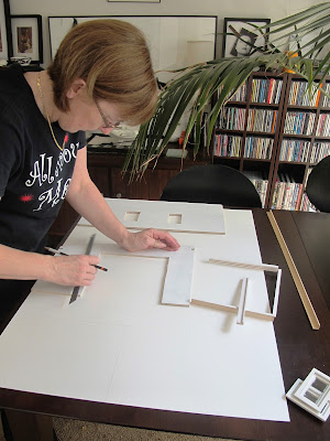 Woman positioning dolls' house kit walls onto of a large piece of mat board.