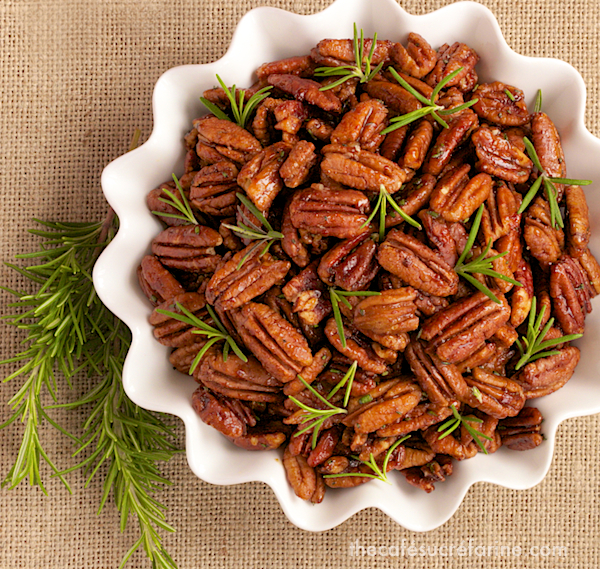 Overhead photo of a white dish of Sweet and Spicy Roasted Pecans on a tan woven placemat.