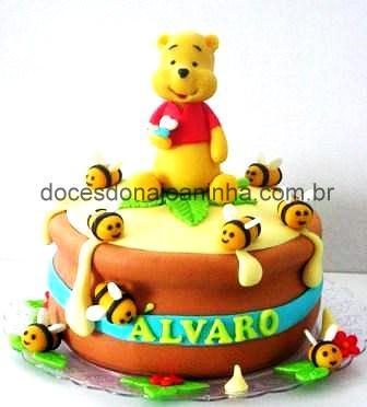 Bolo decorado do Ursinho Pooh num pote cheio de mel, cercado de abelhinhas.