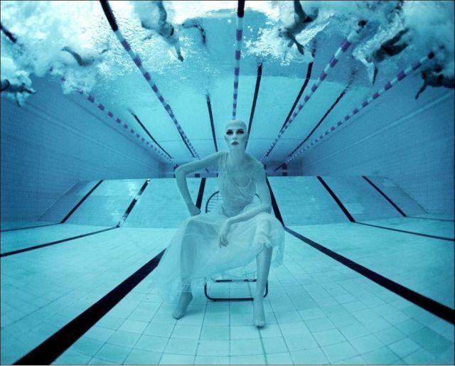 Pessoa sentada debaixo d'água durante natação