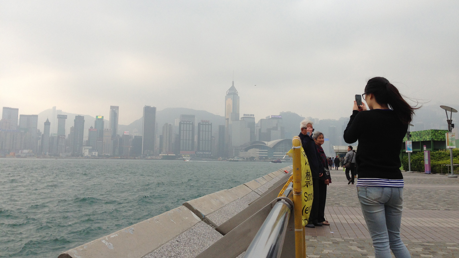 The weather may be foggy, but it hasn't stopped this woman from taking a photo of Hong Kong Island's skyline.