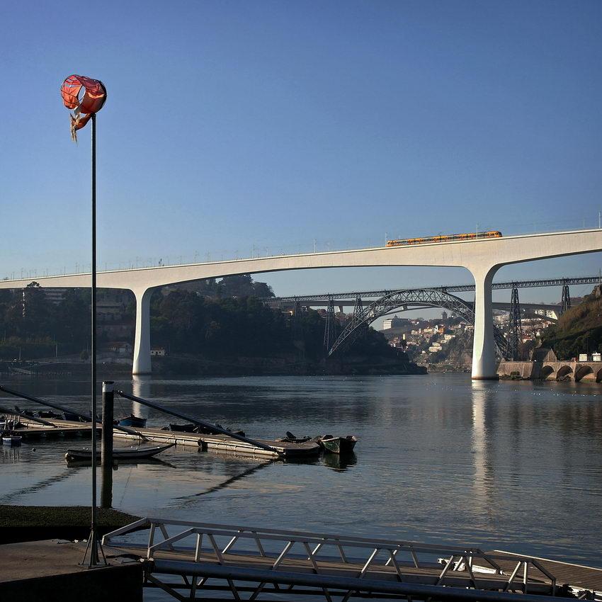 Foto com o ancoradouro em primeiro plano, a seguir a ponte de São João, com um comboio a passar e por fim a ponte de Dona Maria e ponte do Infante