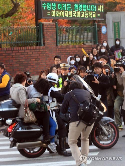 Estudiante coreana llega al centro de examen en la moto de un policía