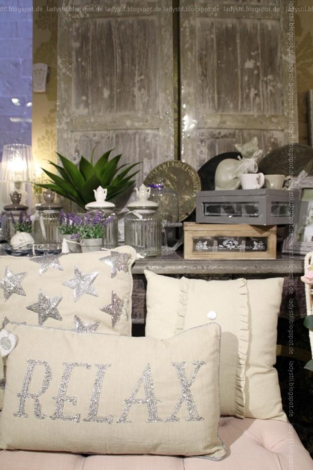 Drei beige Kissen eins mit Schriftzug Relax in silber eins mit silbernen Sternen vor einer Kommode mit Interior Deko