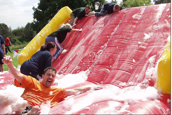 Man sliding down inflatable in foam