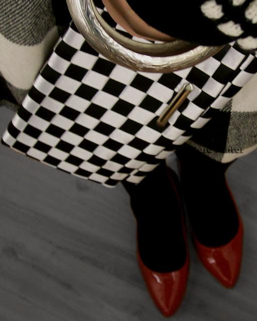 De cima para baixo, ocupando o centro da metade superior da imagem, uma carteira feminina em preto e branco, segurada em diagonal junto à saia xadrez em preto e branco. Vistos a parte superior do pulso de uma pessoa de pele branca, segurando a carteira, a parte de uma pulseira grossa de metal prata e o punho da blusa de lã preto e branco. Na metade inferior da imagem, meia de lã preta cobre canelas e pés, calçados com sapatos vermelhos brilhosos, posicionados no canto inferior direito da imagem. Piso cinza.
