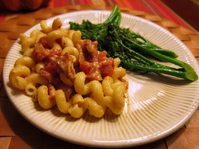 Pasta with a sauce of tomatoes, ricotta and bacon, served with broccolini