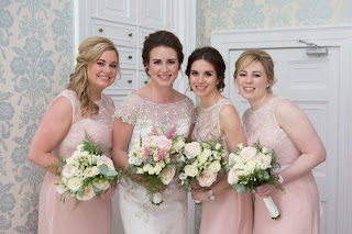 the bride and her bridesmaids in pastel coloured gowns with wild flower bouquets