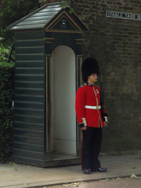 British soldier wearing red tunic and bearskin outside Clarence House London
