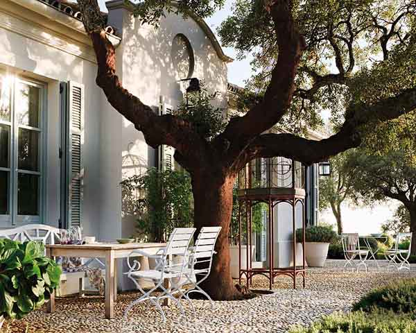 Una de las fachadas con el gran arbol y muebles de jardín