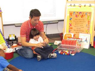 Alex está sentado no chão com seu aluno no colo.  Foto de Carla Guarilha.