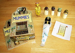 Our completed mummy, canopic jars and cat coffin. Tessa and I stuck the amulet stickers onto cardboard remnants left over from the canopic jars and then I cut around them so she can play with them again and again.