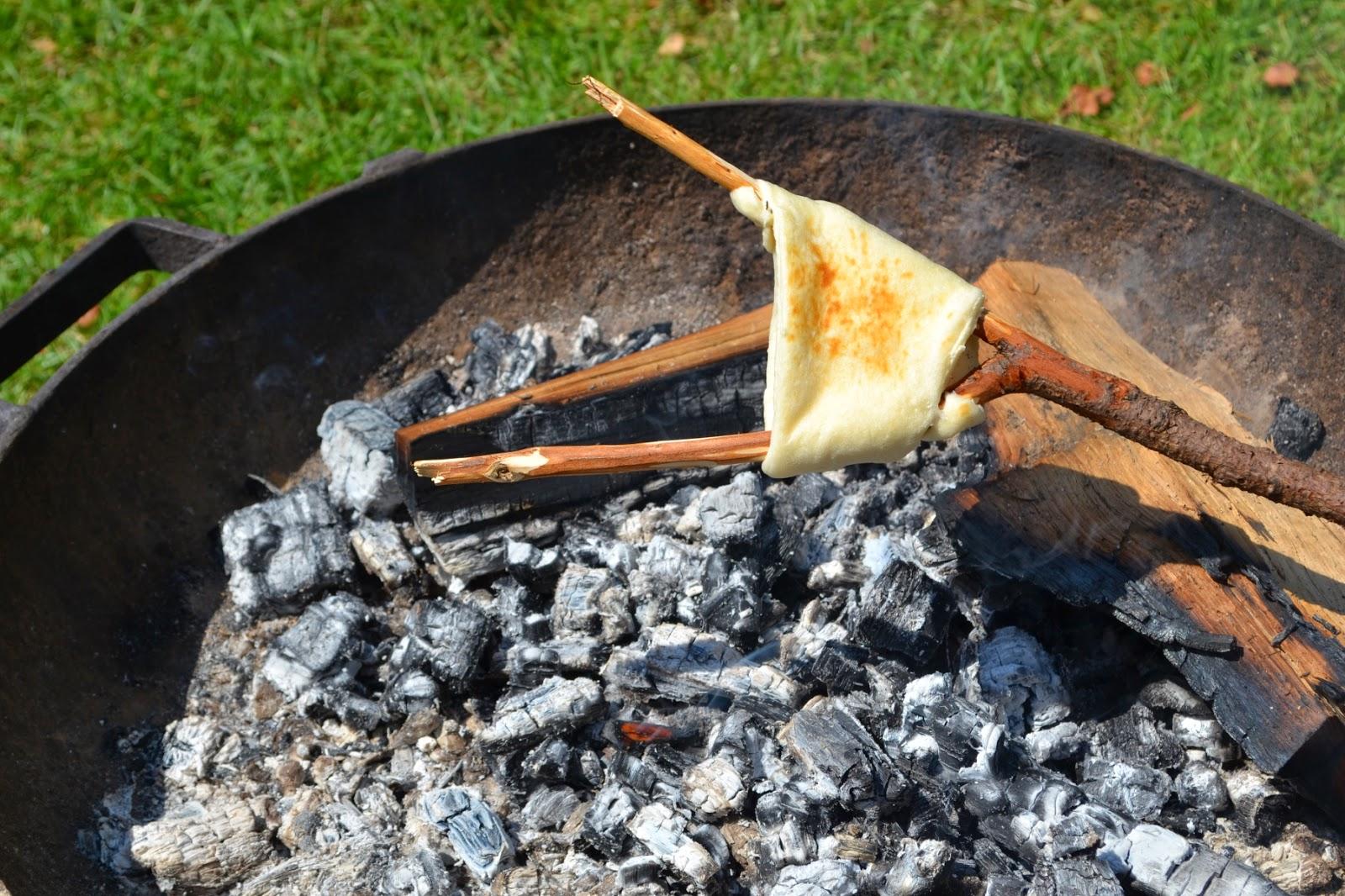 Vorkstok met al iets gebakken croissantdeeg boven een bak hete houtskool