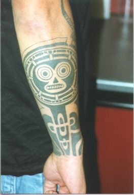 Tribal arm tattoo with strange face