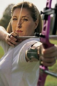 Picture of a lady wearing an arm guard while shooting her bow