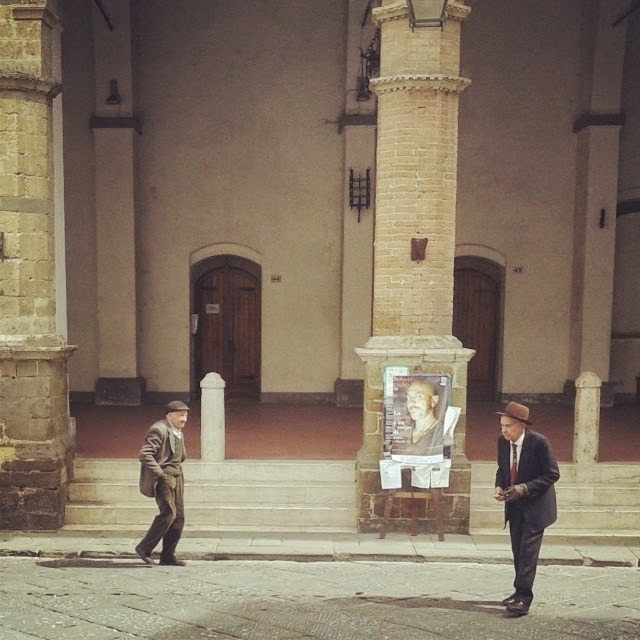 Two old and well dressed Italian men crossing Montalcino's town square