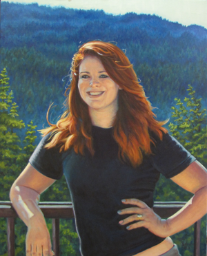 Red haired young lady posed with hand on hip in front of mountain scenery.