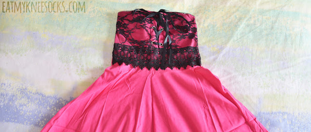 Details on Dresslink's pink strapless tube skater dress, with a lace trim accent, ribboned lace-up tie front, and flared skirt.