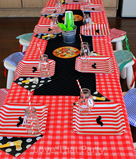 party table with red check table cloth stripe paper plates pizza party theme milk bottles paper straws and party printables all personalised with name