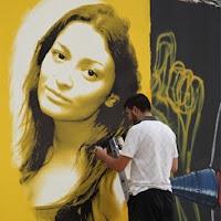 Um artista está fazendo graffiti na parede amarela.