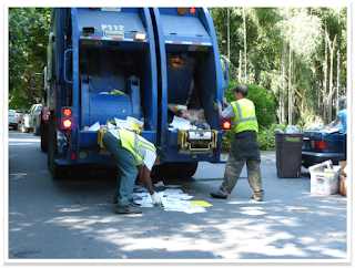 Recycling crew collecting loose paper from the street.