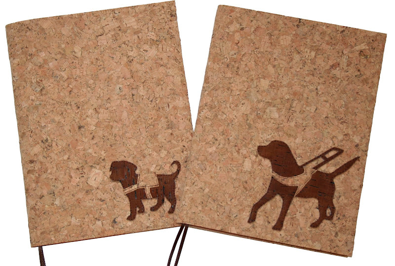 two cork covered journals, one with a puppy in training wearing service jacket and one with a working lab in harness