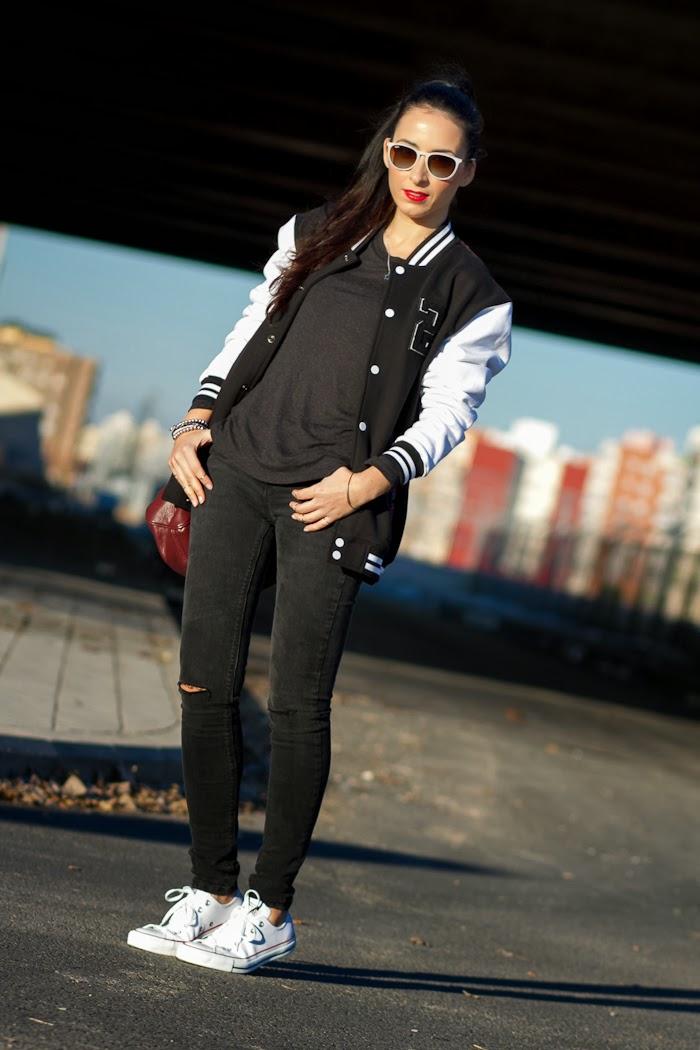 Look cómodo estilo deportivo con zapatillas de cuero converse blancas, pantalones rotos de Zara y chaqueta de beisbol bicolor