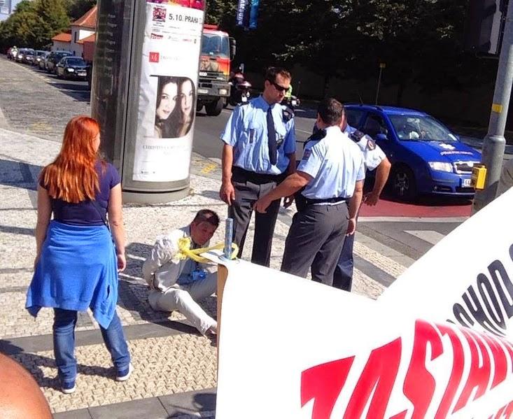 (上图二)中使馆官员对法轮功学员施暴被捷克警察铐住(明慧网)