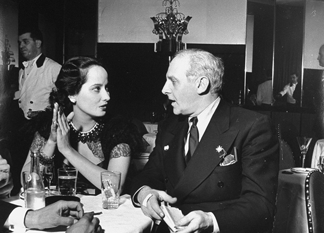 Merle Oberon y Walter Winchell conversan en la Cub Room. Imagen vía LIFE© | John Phillips – Time & Life of Pictures/Getty Images