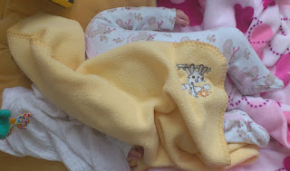 three month old baby hides under yellow blanket