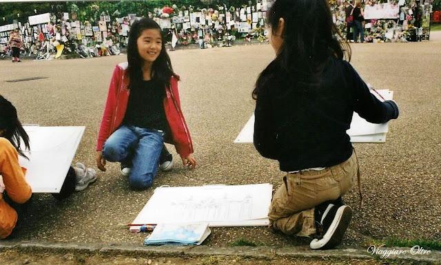 Bambine intente a disegnare di fronte al cancello di Kensington Palace pieno di dediche e fiori