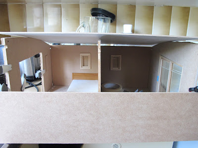 Front view of a dolls; house miniature shed kit, held together with clamps and tape, with a piece across the front.
