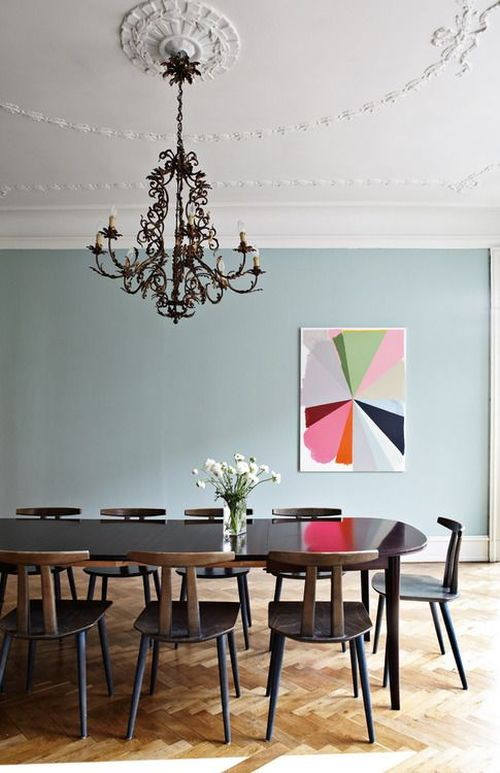 simple and colorful dining area with bright painting