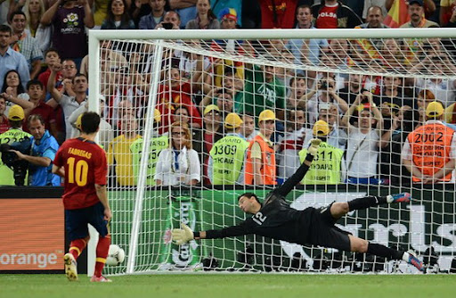 Spanish midfielder Cesc Fàbregas scores the winning penalty past Portuguese goalkeeper Rui Patrício