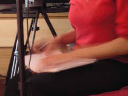 Dolmetscherhände in Bewegung, Füller, Papier, neben einem ruhigen Kamerastativ