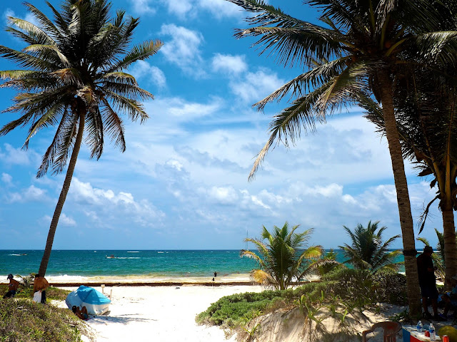 Palm trees, white sand and turquoise ocean at the beach at Tulum, Mexico