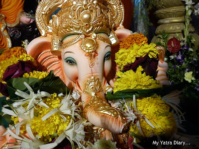 Ganpati idol decorated with flowers in a pandal of a society