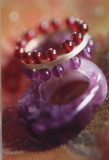 A ring created by Sylvie Pelissier, embellished with a double band of amethyst and garnet beads. The unpolished amethyit ring shows the different shades of this Stone from extremely pale mauve to intense violet.